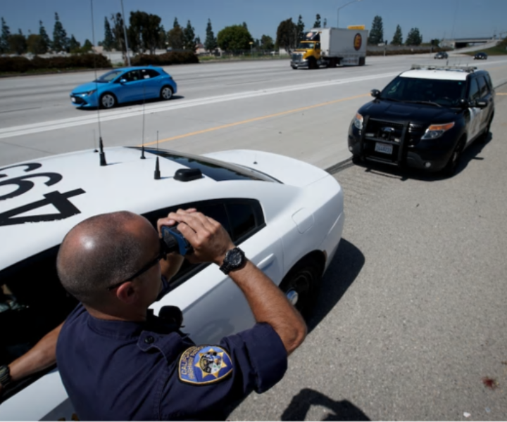 California Highway Patrol officer Matthew Musselmann uses a lidar gun for speed detection along Interstate 5 in Anaheim, Calif., on April 23. Police agencies around the country are reporting a rise in speeding tickets. (Chris Carlson/AP)