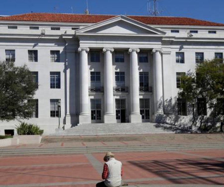A man sits across from Sproul Hall on the University of California campus in Berkeley, Calif., Wednesday, March 11, 2020. (AP Photo/Jeff Chiu)