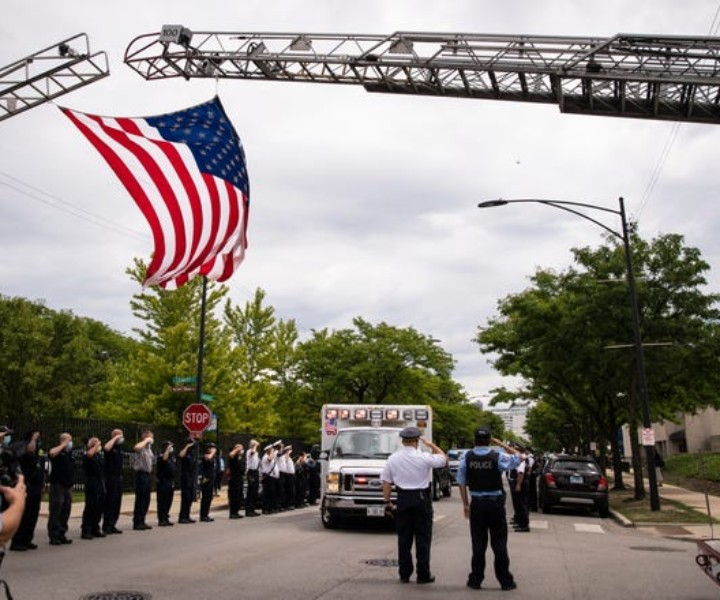 Officers salute outside the Cook County Medical Examiner's office